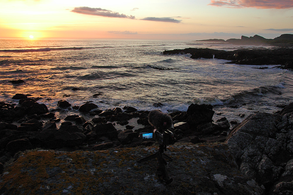 Picture of a sunset being filmed with a small video camera