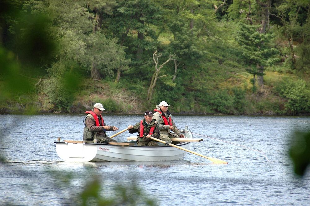Picture of two fly fishing competitors in a boat with a rower