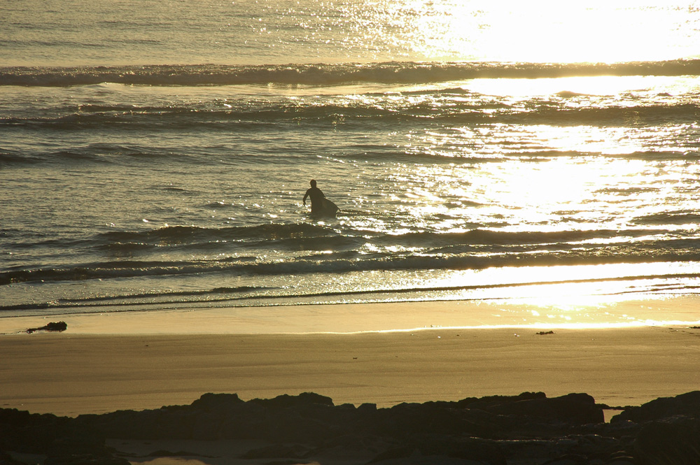 Picture of a man carrying a surfboard out into the sea on a sunny mild evening