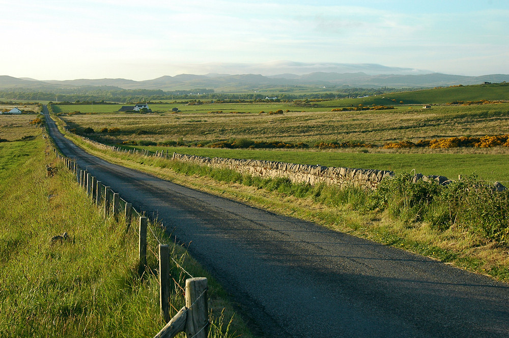 Picture of a straight single track road through countryside with low hills