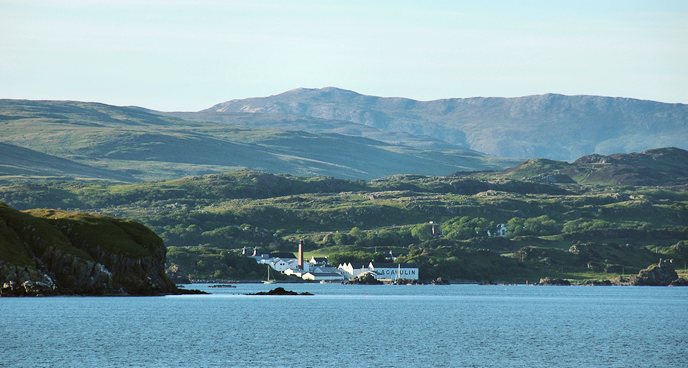 Picture of a coastal distillery seen from an evening ferry