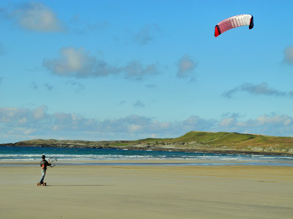 Picture of a man landboarding on a wide beach on a sunny day