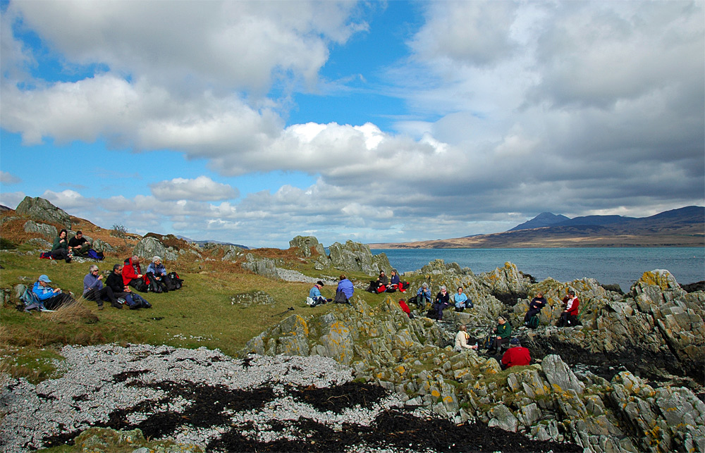 Picture of a group of walkers resting and having lunch near the shore of a sound