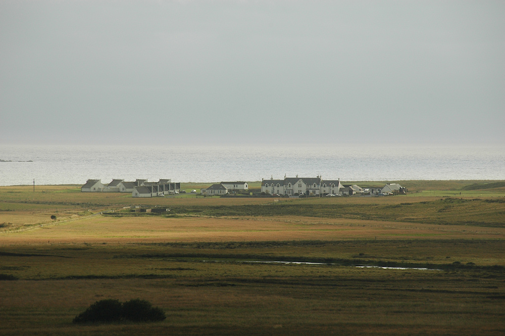 Picture of a hotel and lodges next to a links golf course