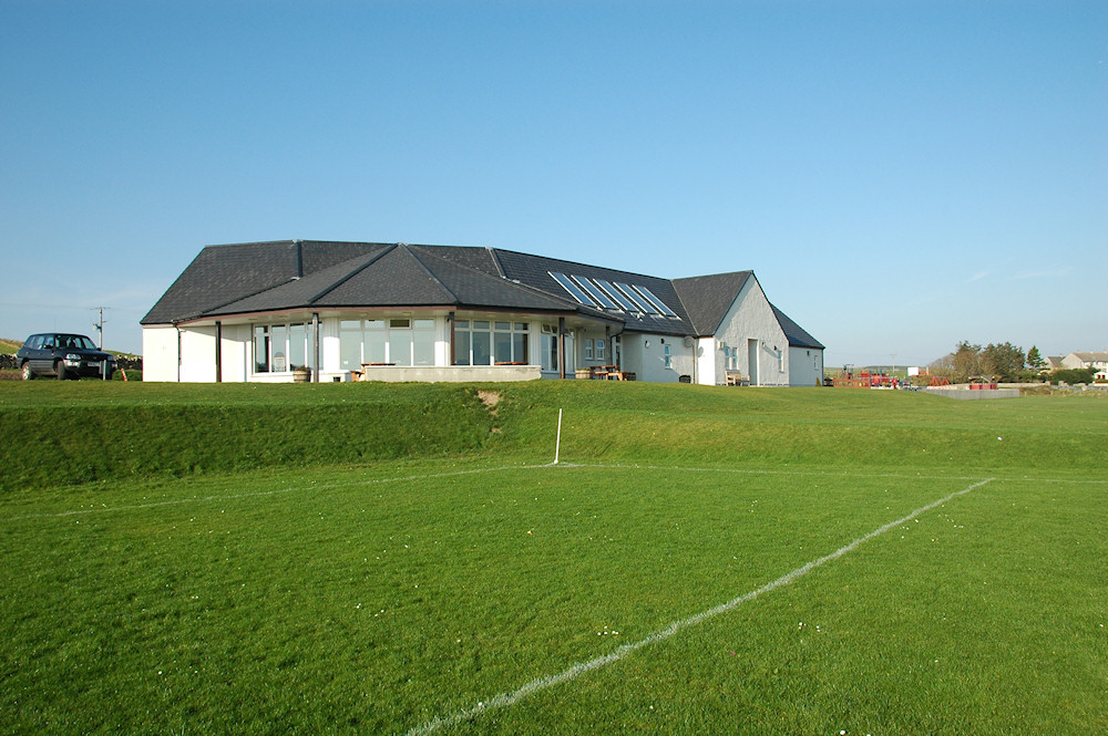 Picture of a community centre and playground next to a football pitch