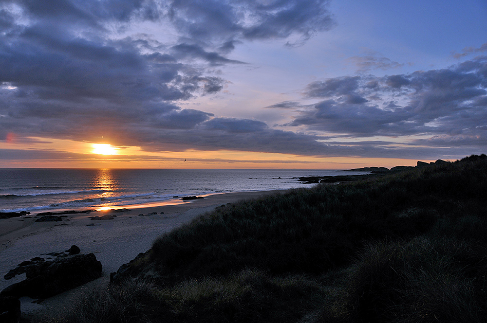 Picture of a cloudy sunset watched from the dunes above a bay