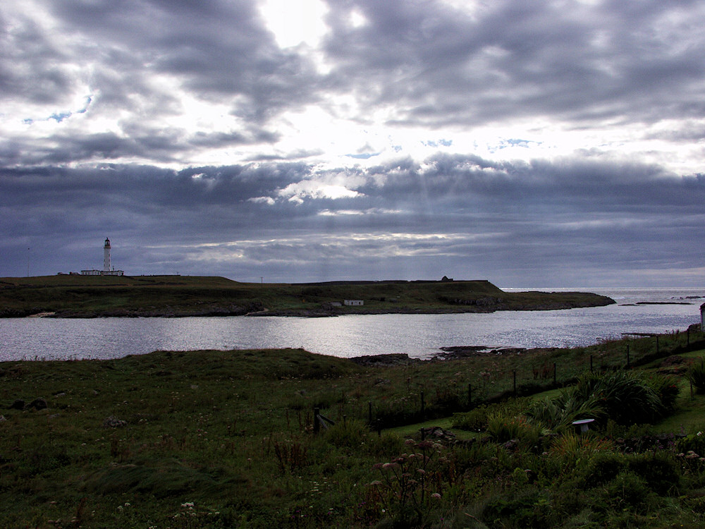 Picture of a small island with a lighthouse, sun breaking through clouds