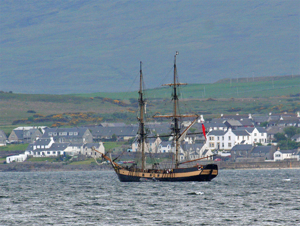 Picture of a tall ship anchored in a sea loch off a small coastal village