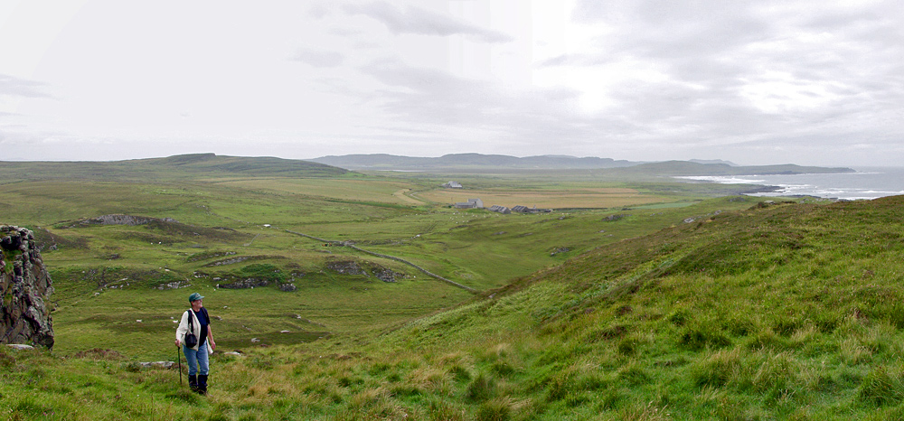 Panoramic view over a coastal landscape from a hill, a walker coming up the hill
