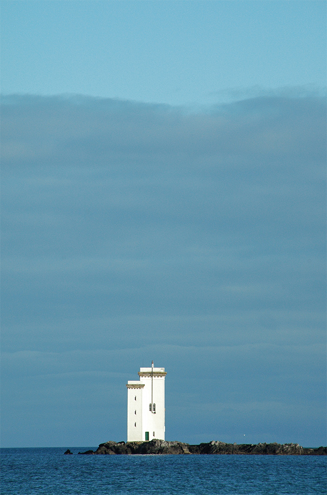 Picture of a lighthouse under a dark cloudy sky, illuminated by the sun from another direction