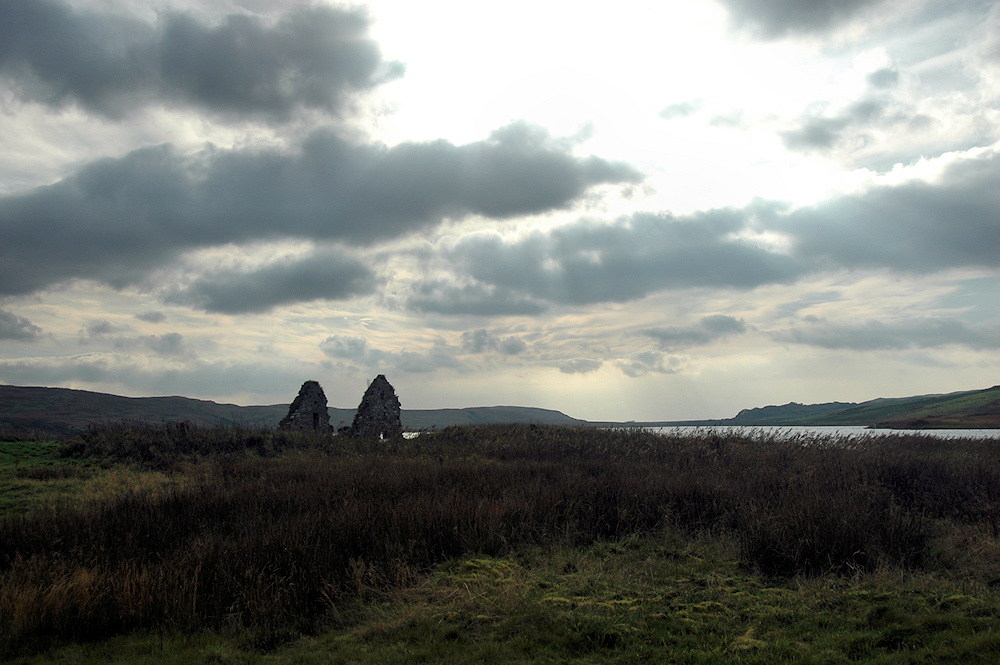 Picture of a ruin on a small island in a lake, the sun breaking through clouds