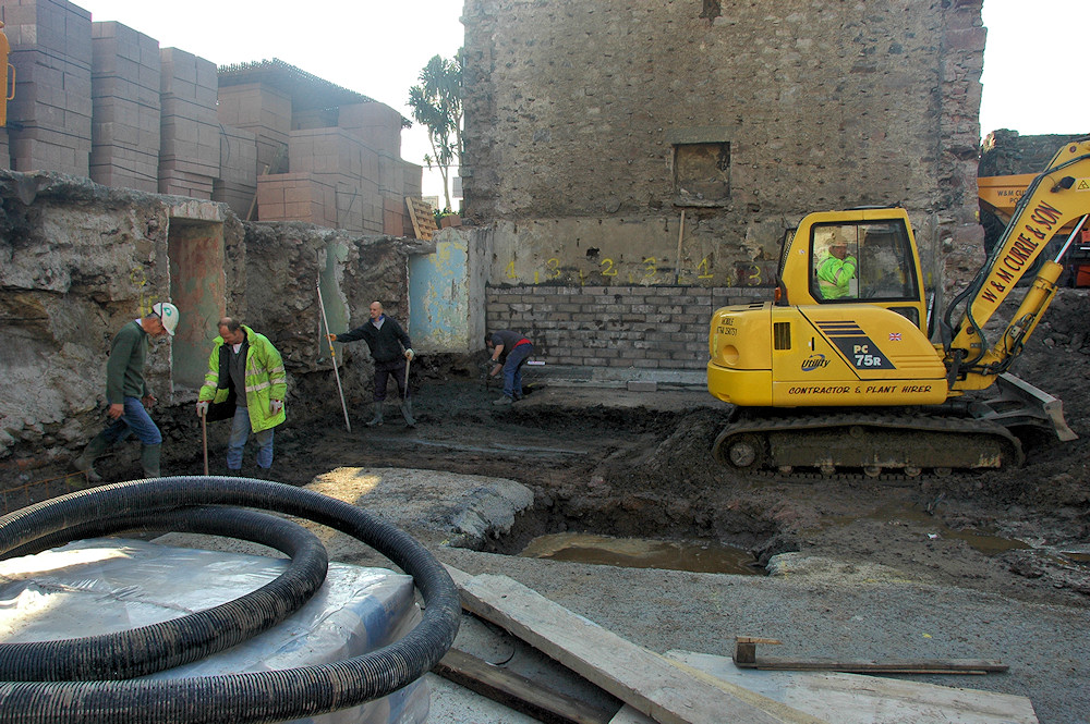 Picture of the start of the construction of a hotel, a hole in the ground for the foundations