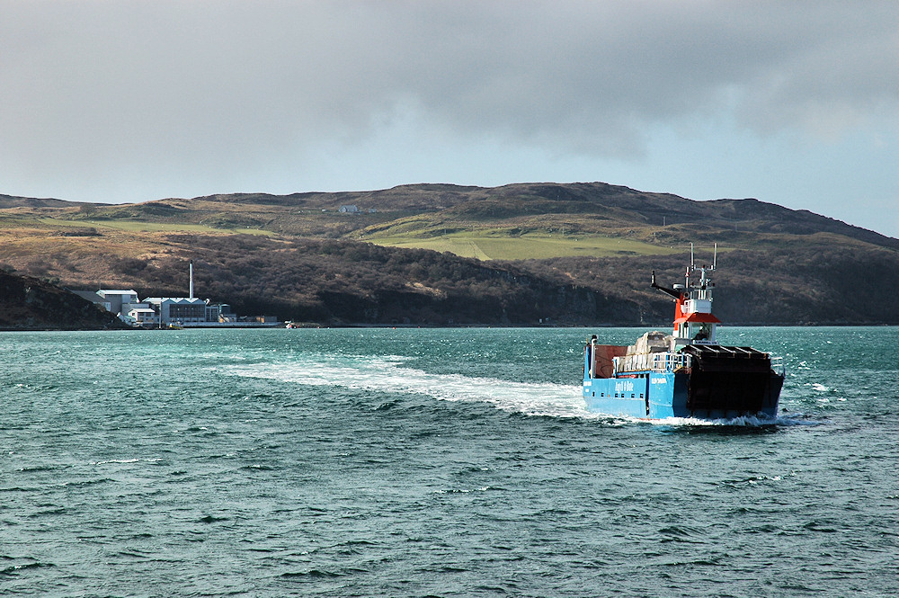 Picture of a small ferry on a sound between two islands, a distillery on the side