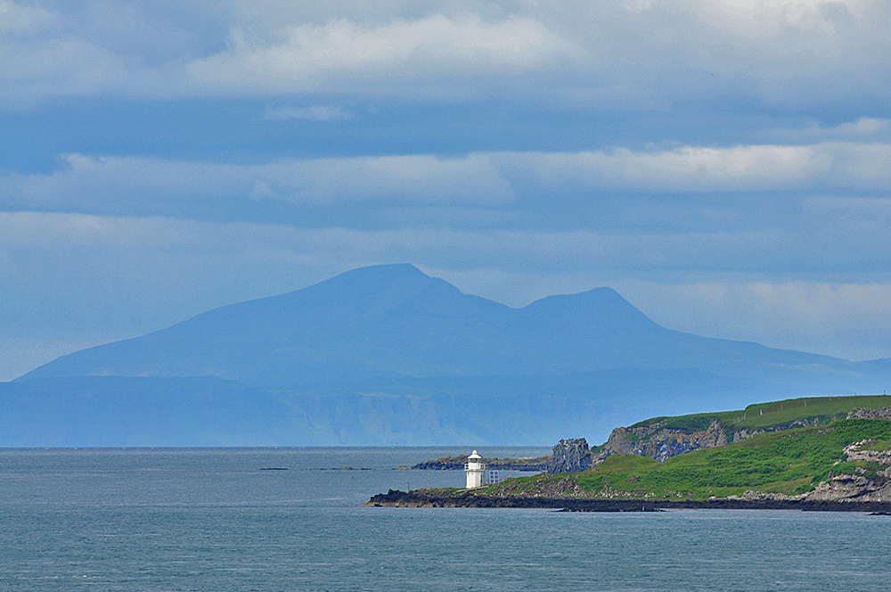 Picture of a small lighthouse on an island, another island with a mountain in the distance behind