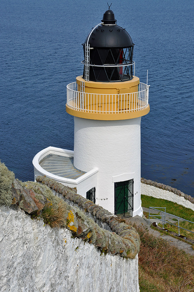 Picture of a lighthouse high above  the sea