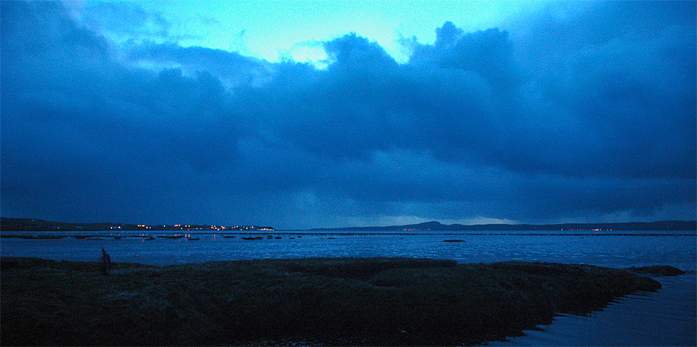 Picture of a sea loch with a few coastal villages at last light