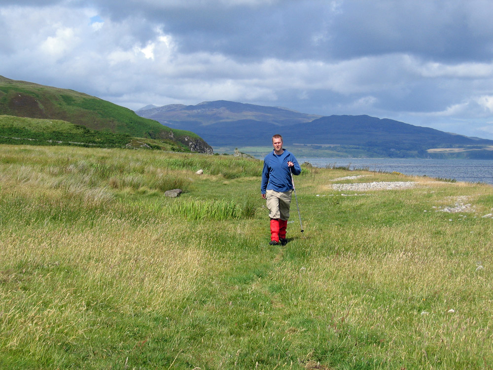 Picture of a man walking on a rough grassy path close to a shore
