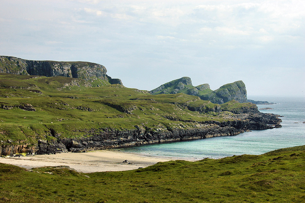 Picture of a small beach with some distinctly shaped hills and cliffs behind