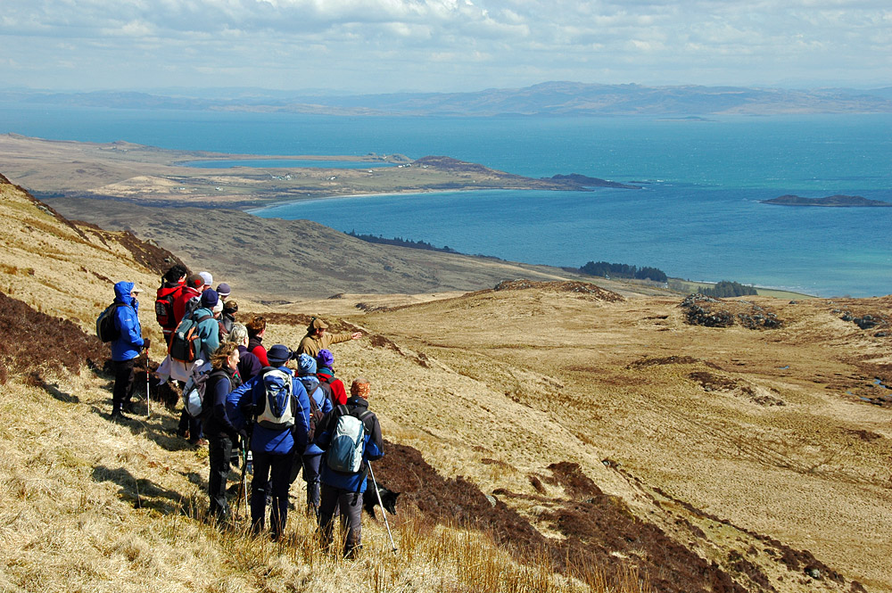 Picture of a group of walkers on a hillside high above two coastal bays