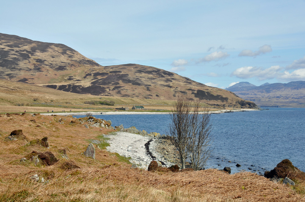 Picture of a coastal landscape with a bothy in the distance, a few walkers on their way to the bothy