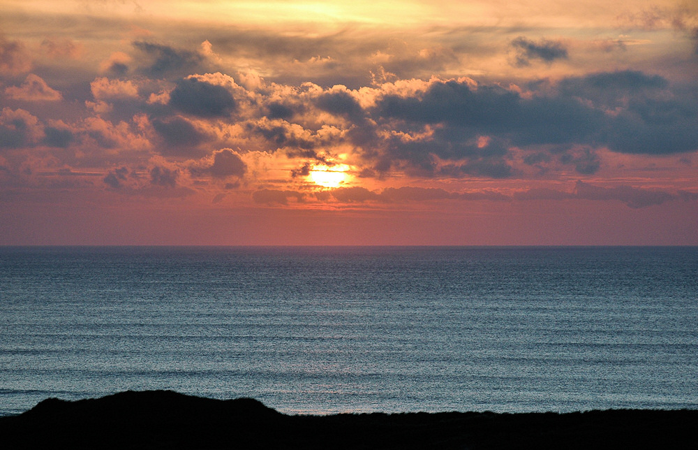 Picture of a colourful sunset on  a cloudy day, seen across the sea from the top of dunes