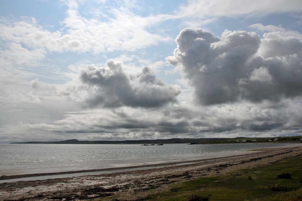 Picture of a sea loch in hazy sunshine with some big dramatic clouds moving in