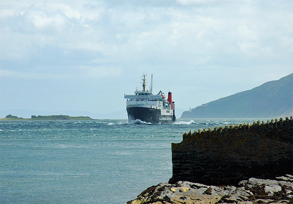 Picture of a ferry approaching along a sound between two islands, a lighthouse in the distance
