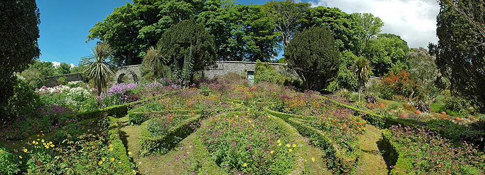 Panoramic picture of flower beds in a walled garden