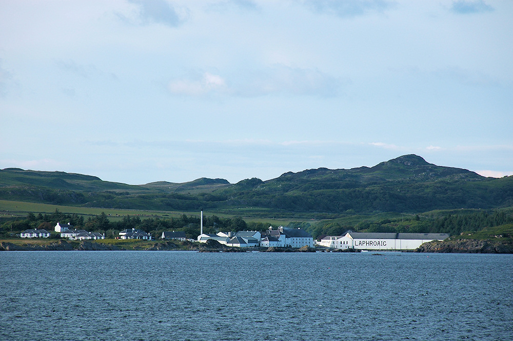 Picture of a coastal distillery (Laphroaig)  seen from a passing ferry