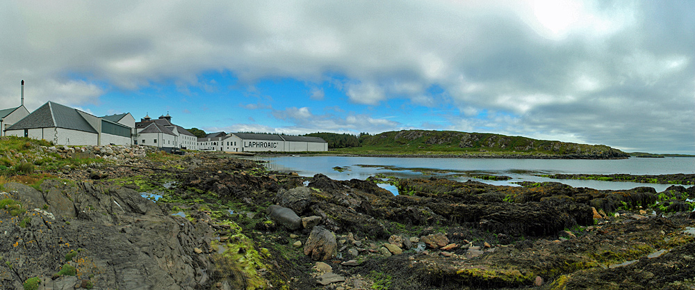 Panoramic picture of a small sea loch with a distillery on the shore
