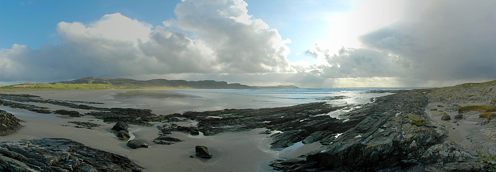 Picture of a panoramic view over a bay with a wide sandy beach, clouds moving in from the side