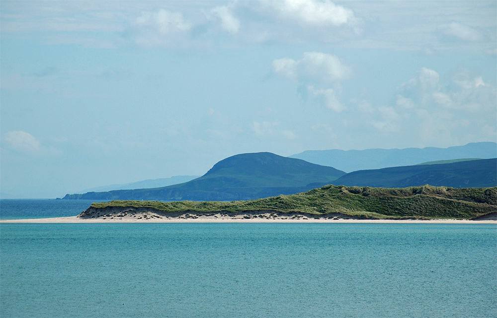 Picture of coastal dunes and a small hill seen across a sea loch
