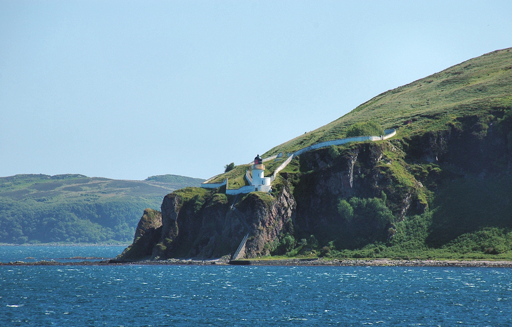 Picture of a lighthouse on top of steep cliffs on a bright and sunny day