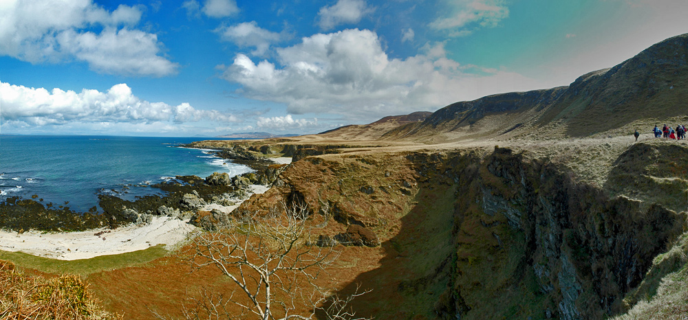 Panoramic picture of raised beaches on a remote shore, walkers on the edge