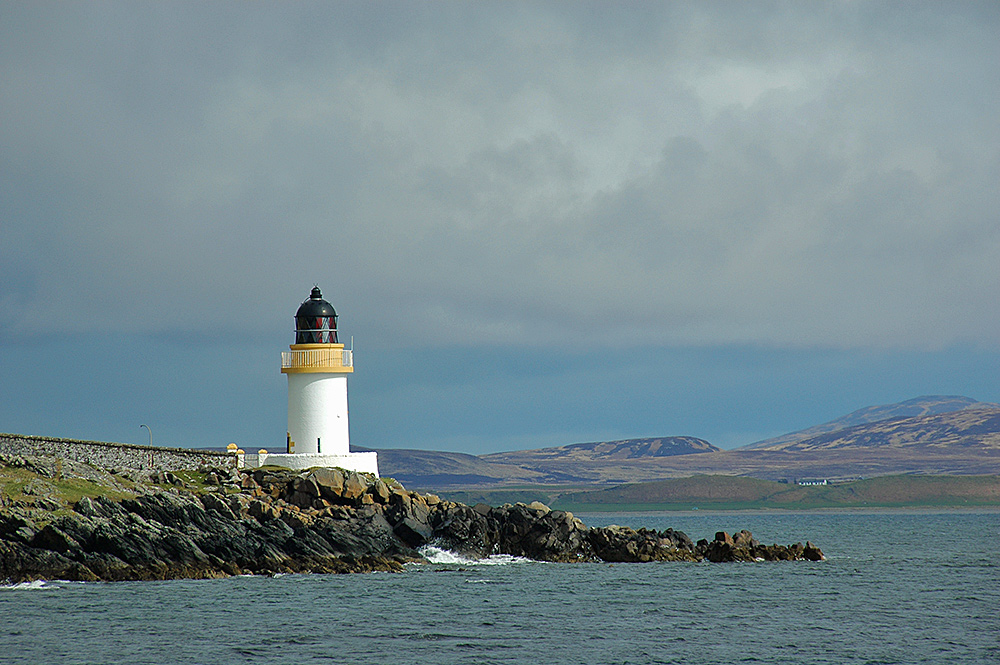 Picture of a small lighthouse at a sea loch in the sunshine with dark clouds moving in above