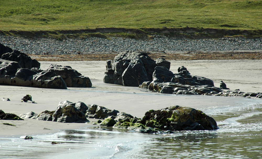Picture of rocks on a sandy beach in the sunshine
