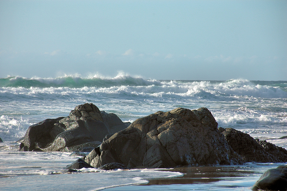 Picture of waves rolling on to a beach with some rocks, the wet rocks glistening in the sun