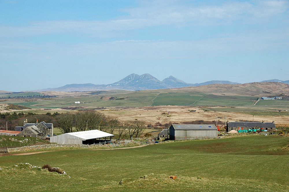 Picture of a farm in a hilly landscape, larger mountains in the distance