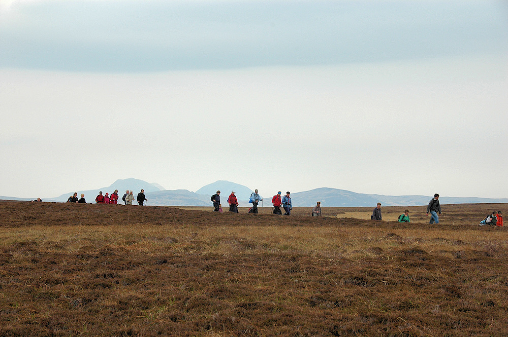 Picture of a line of walkers walking through a heathery wide open landscape, some large mountains in the distance