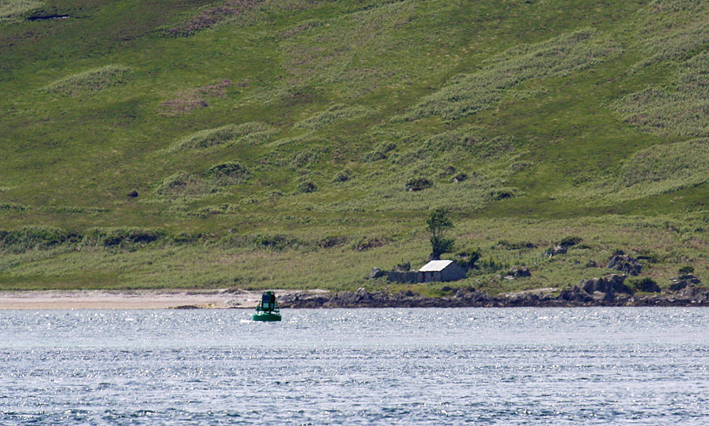 Picture of a small bothy seen across a sound between two island