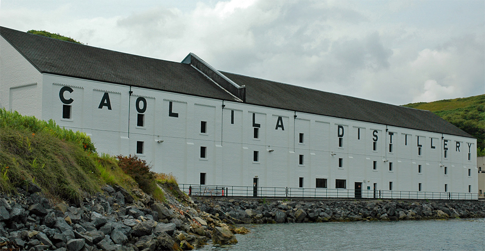 Picture of a large whitewashed whisky warehouse  at a shore