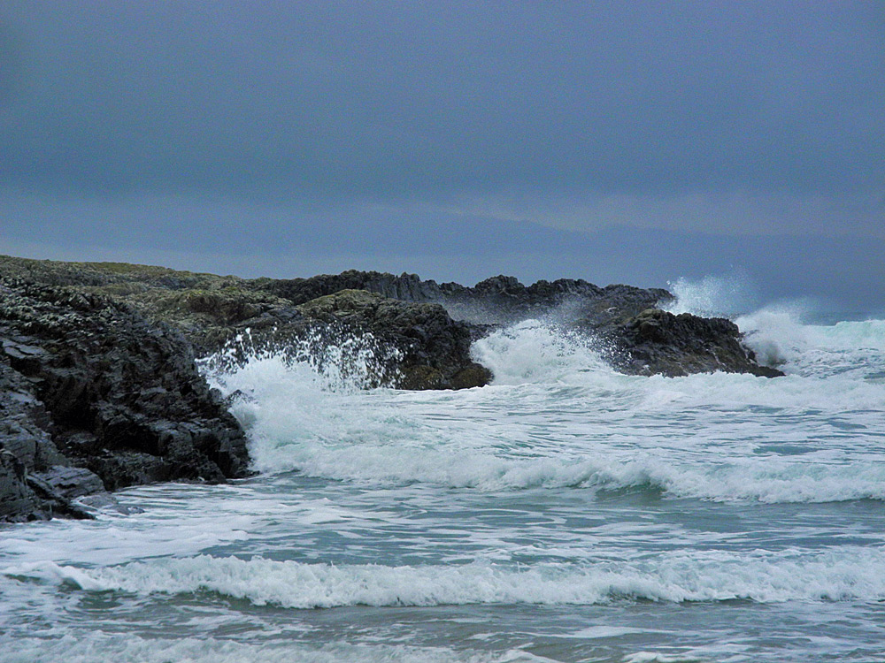 Picture of waves breaking over rocks under a dark sky