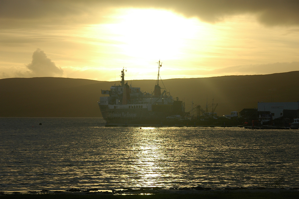 Picture of a ferry moored at a pier against a low evening sun
