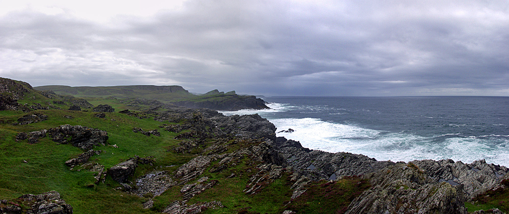 Picture of remote cliffs under dark clouds with waves breaking against them