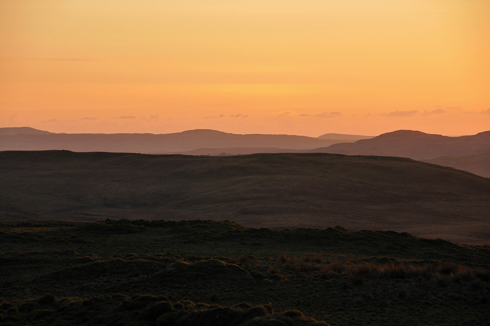 Picture of a hilly landscape in mild orange evening light