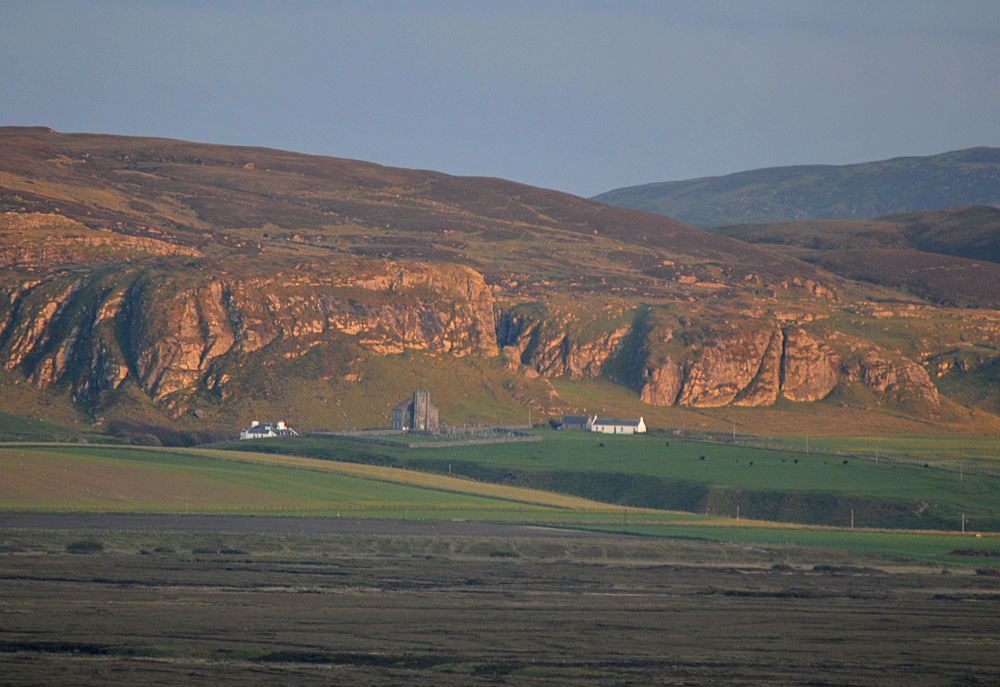 Picture of a church and a few houses in front of steep crags in the mild evening light
