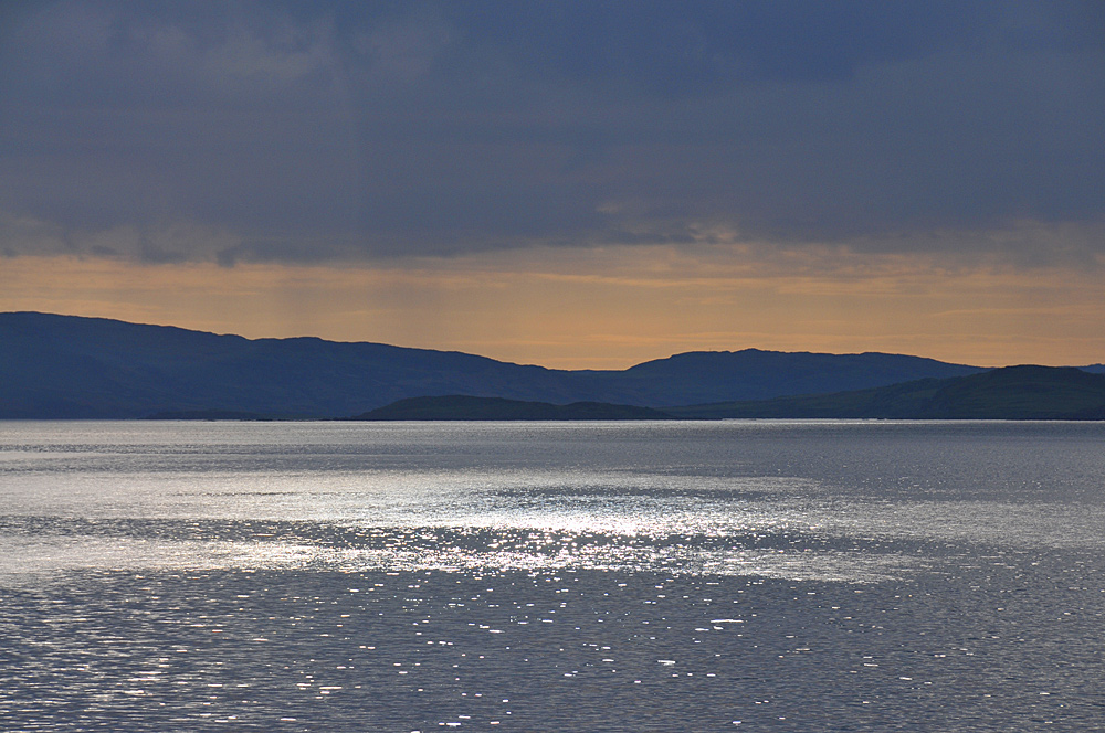 Picture of sunlight reflecting on the sea under a dark sky, seen from a ferry