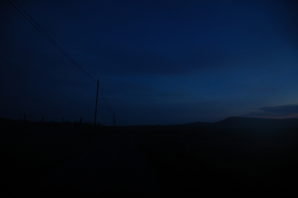 Picture of a single track road at night with the last light still illuminating the sky