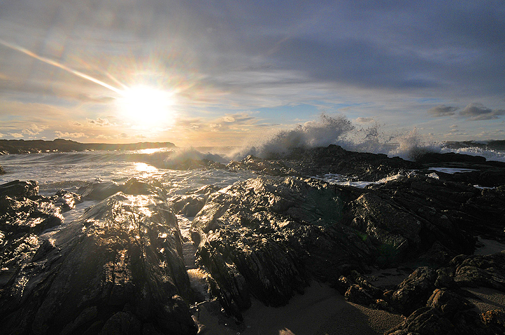 Picture of a wide angle view of a wave splashing over rocks in a bay, low sun behind
