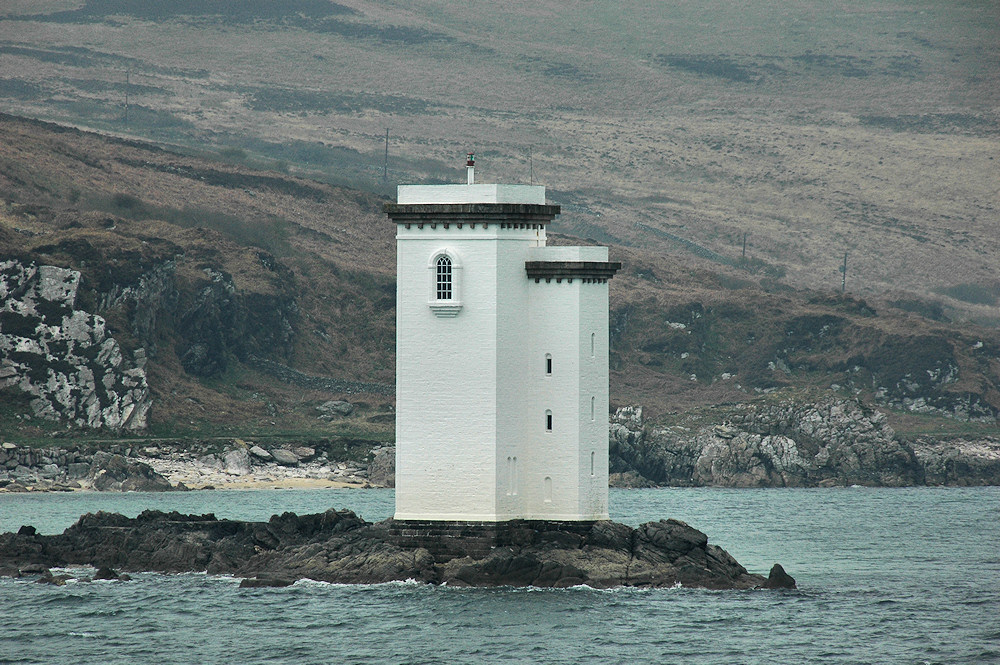 Picture of a square lighthouse taken from a passing ferry